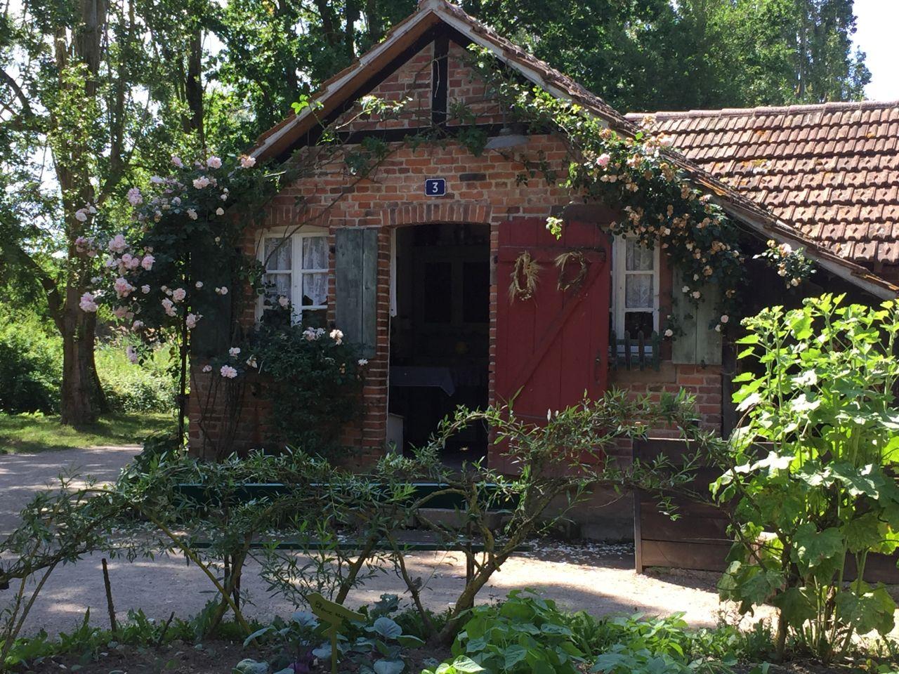 Frontansicht des Arbeiterhauses Monswiller im Écomusée d'Alsace. Ein kleines Backsteingebaeude mit roter Tuere und gruenen Fensterlaeden., davor ein Gemuesegarten