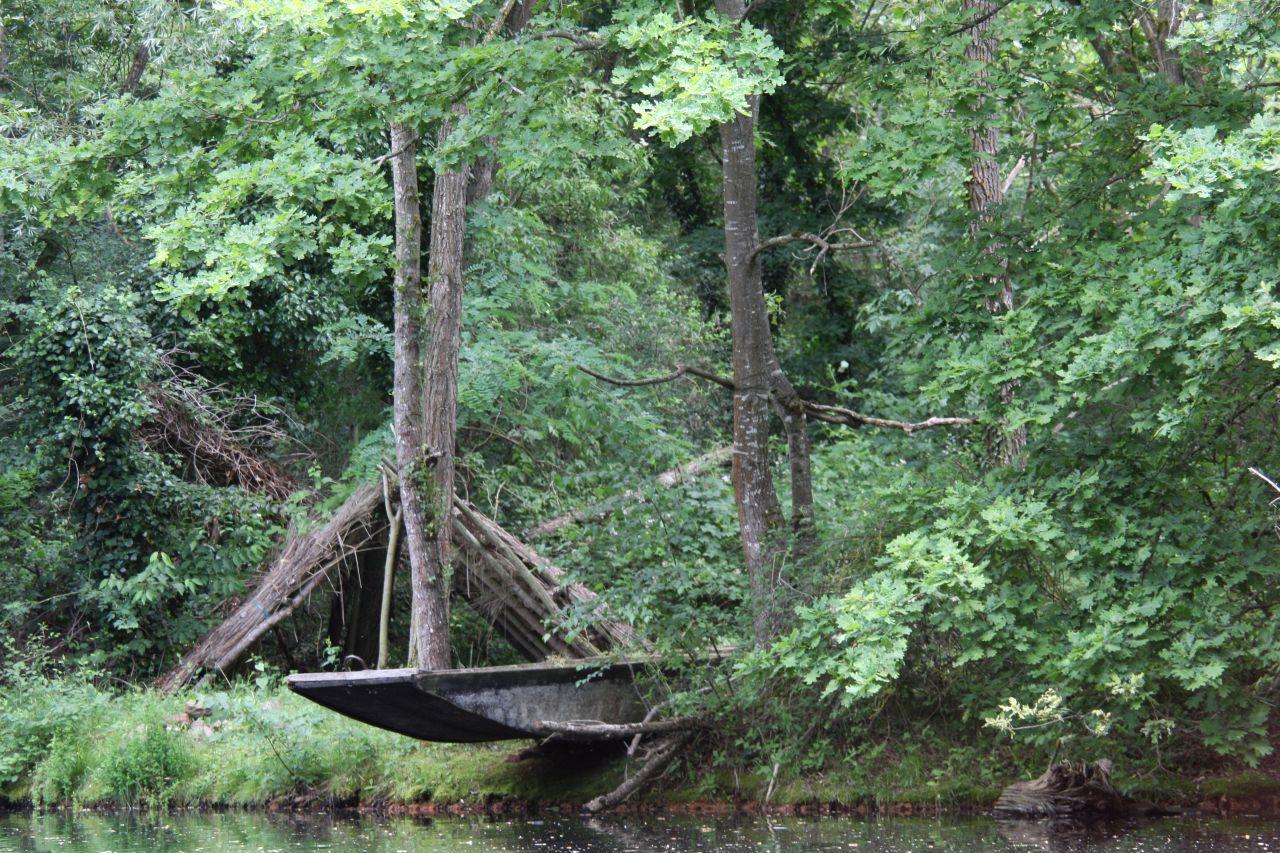 Eine alte Holzbarke mit Fischerhuette am Flusslauf im Écomusée d'Alsace