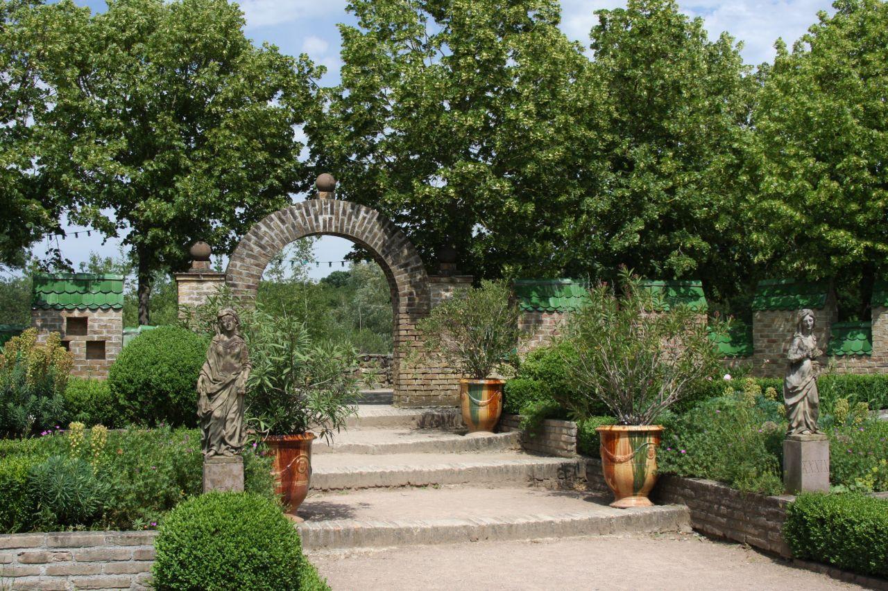 Mit Steinfiguren und riesigen Blumenkuebeln dekorierter Renaissancegarten des Befestigungsturms aus Mulhouse im Écomusée d'Alsace