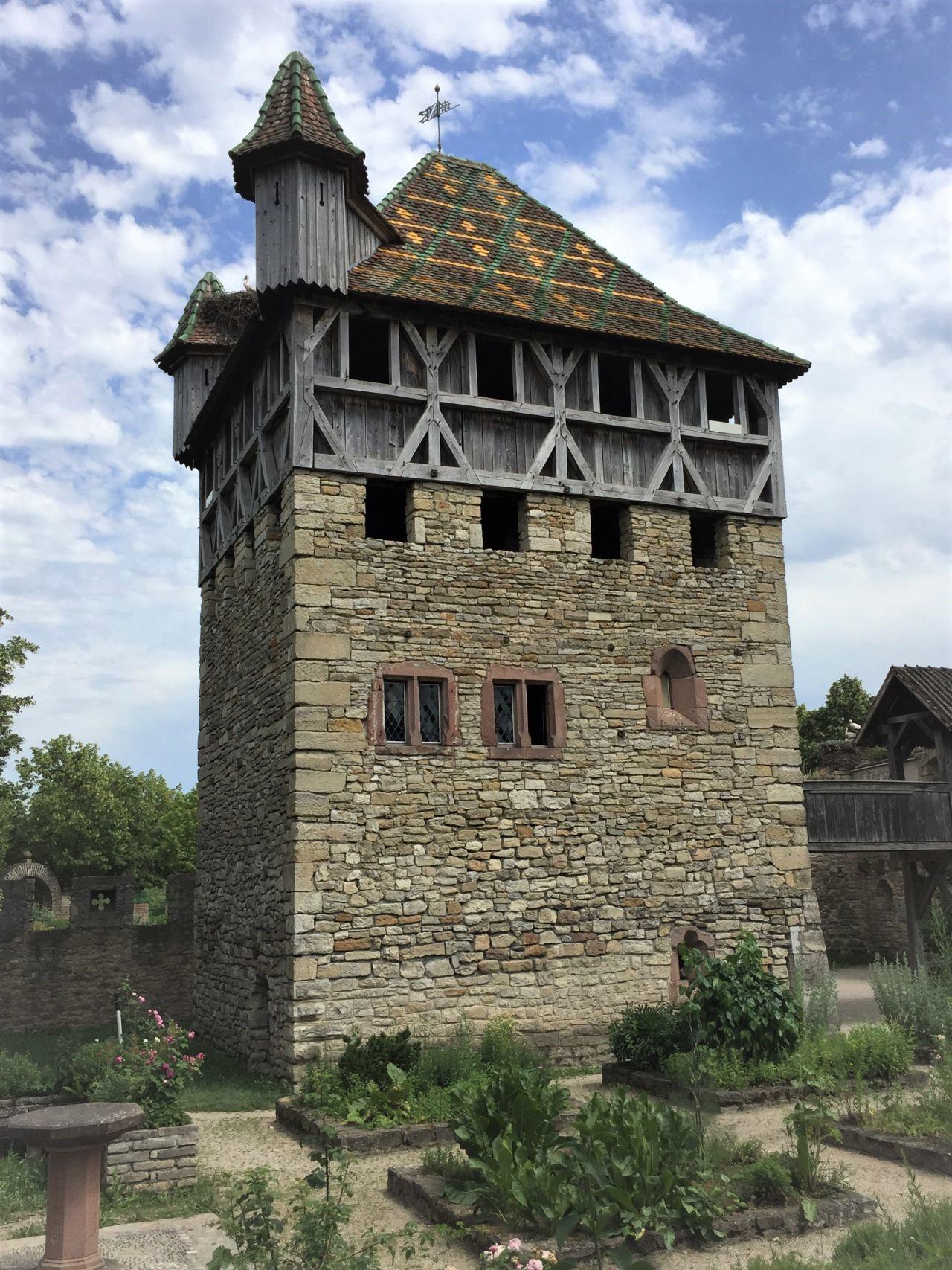 Befestigter Wohnturm aus Mulhouse im Écomusée d'Alsace. Der Turm ist dreistoeckig, hate einen rechteckigen Grundriss und bunt lasierte Dachziegel.
