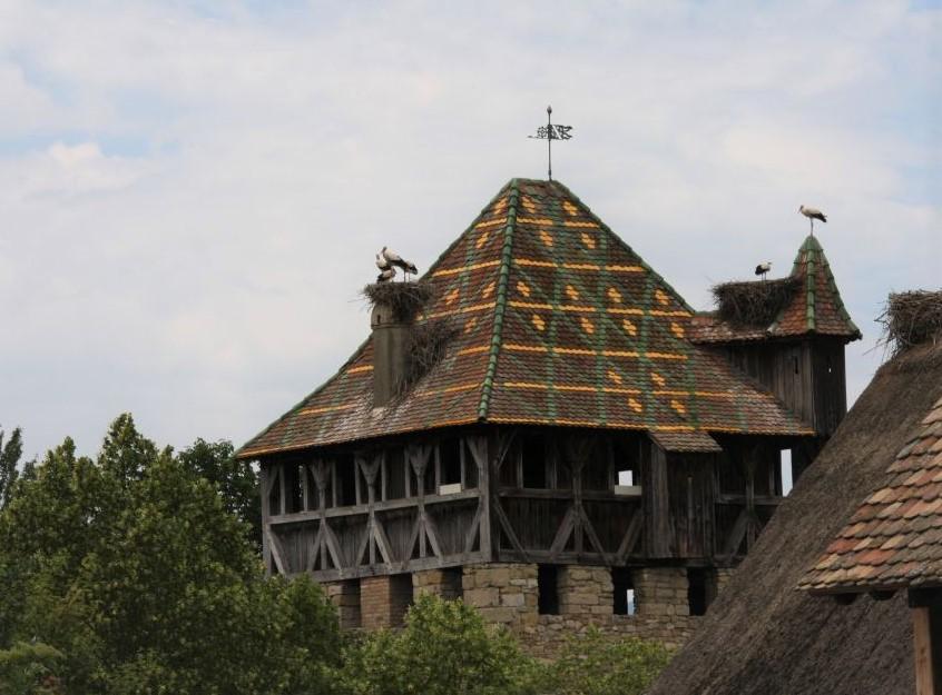 Das hoechste Gebaeude im Écomusée d'Alsace. Der befestigter Wohnturm aus Mulhouse mit seinen lasierte Dachziegel.n udn einem vollbesetzten Storchennest