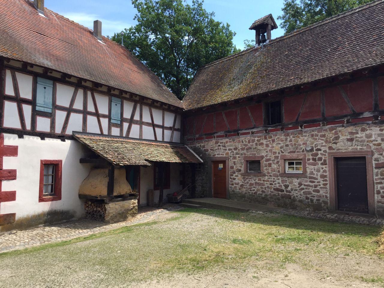 Links das Wohnhaus mit dem Brotofen. Im rechten Winkel dazu die Scheune mit ebenfalls gemauertem Erdgeschoss . Beide Gebaeude gehoeren zum Gehoeft von Rumersheim steht im Écomusée d'Alsace.