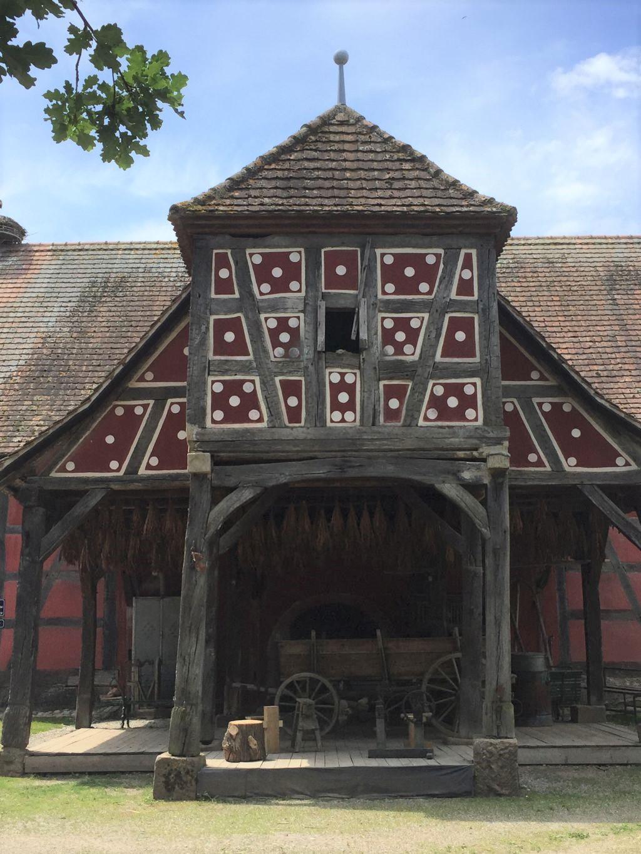 Taubenschlag auf Stelzen, darunter haengt Tabak zum Trocknen. Der weißgepunktete Taubenschlag auf rotem Fachwerk ist aus Oberhergheim und steht im Écomusée d'Alsace.