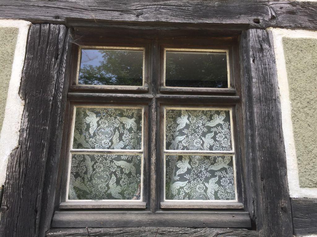 Holzfensterrahmen aus dem 19. Jahrhundert mit Spitzengardine im Écomusée d'Alsace.