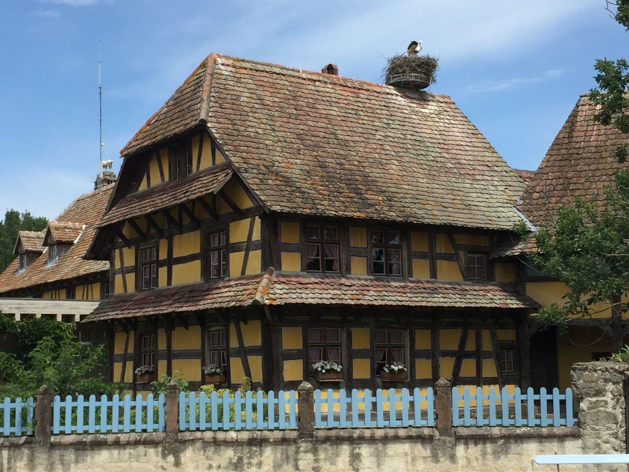 Imposantes, gelbes Fachwerkhaus mit Storchennest auf dem Dach im Écomusée d'Alsace.