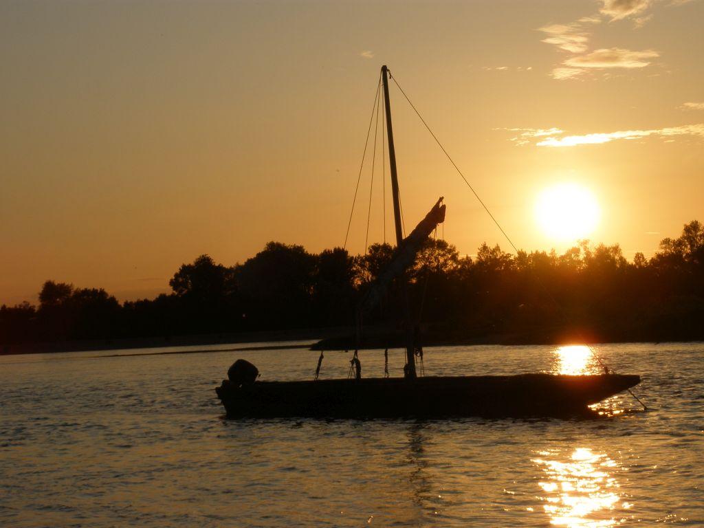 Sonnenuntergang an der Loire mti einem traditionellen Segelboot im Vordergrund