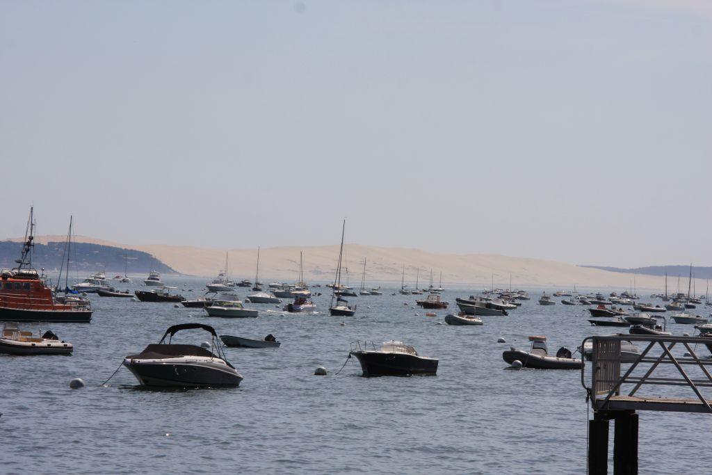 Zahlreiche Boote schaukeln im Becken von Arcachon. Im Hintergrund ist die Wanderduene von Pila zu sehen.