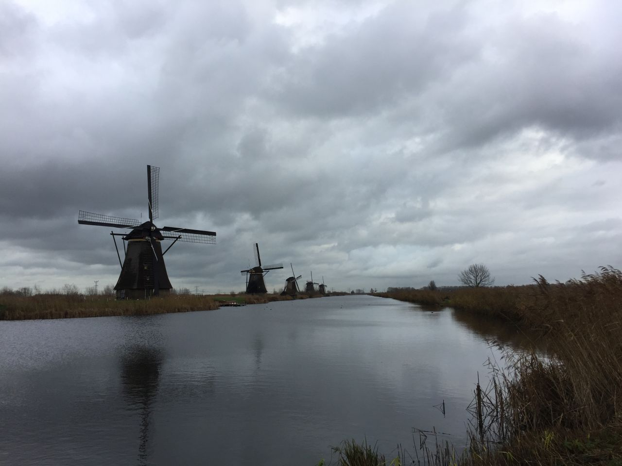 Dunkle Wolken ueber der Muehlenlandschaft am Kinderdijk in den Niederlanden